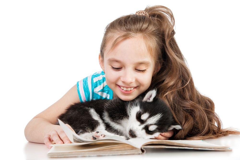 girl reading book with dog