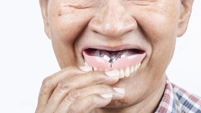 old happy patient wearing dentures