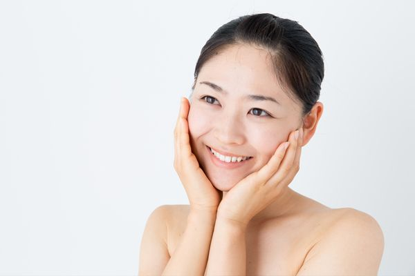 smiling asian woman with hands on her cheeks