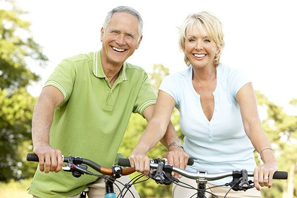 couple smiling while riding a bike