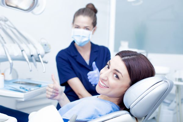 smiling woman with her dentist giving a thumbs up