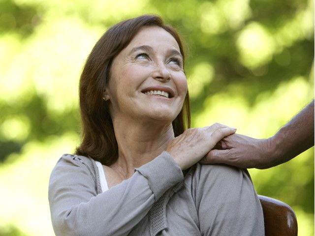 Happy old woman touching someone's hand