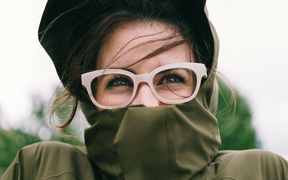Happy girl wear her eye glasses and rain coat