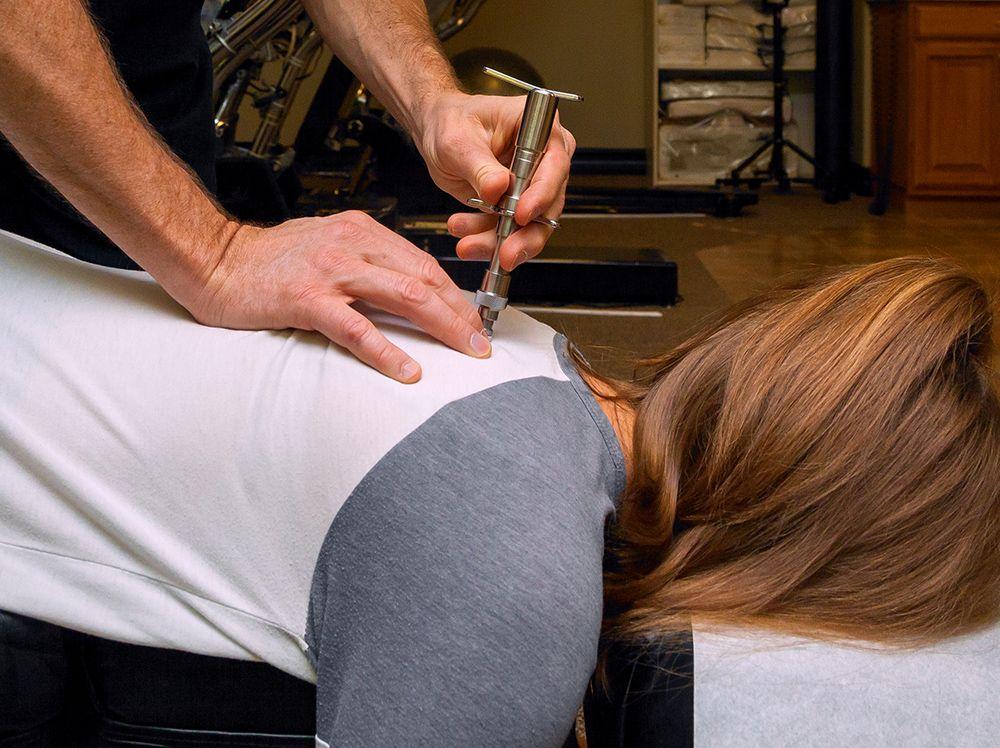 Chiropractor using activator instrument