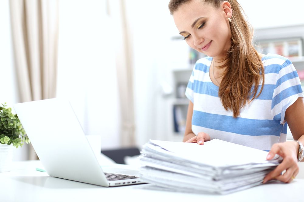 Woman stacking papers in front of a laptop