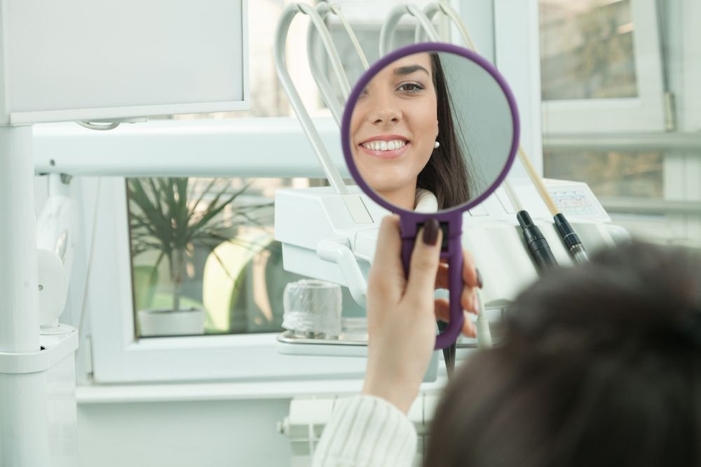 dental patient looking at the mirror after procedure