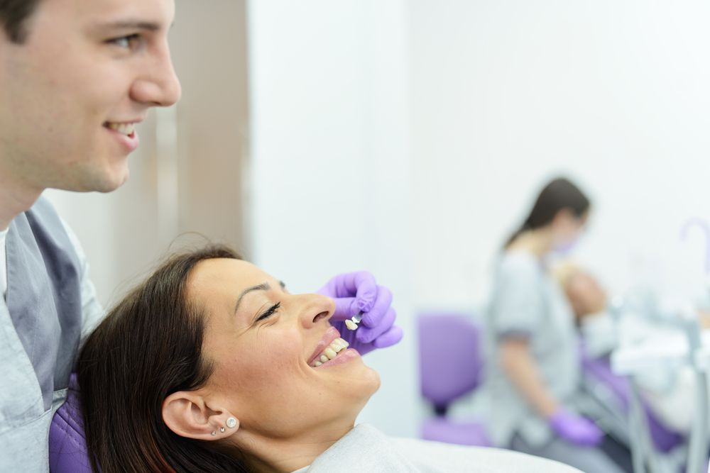 patient choosing veneer color with dentist