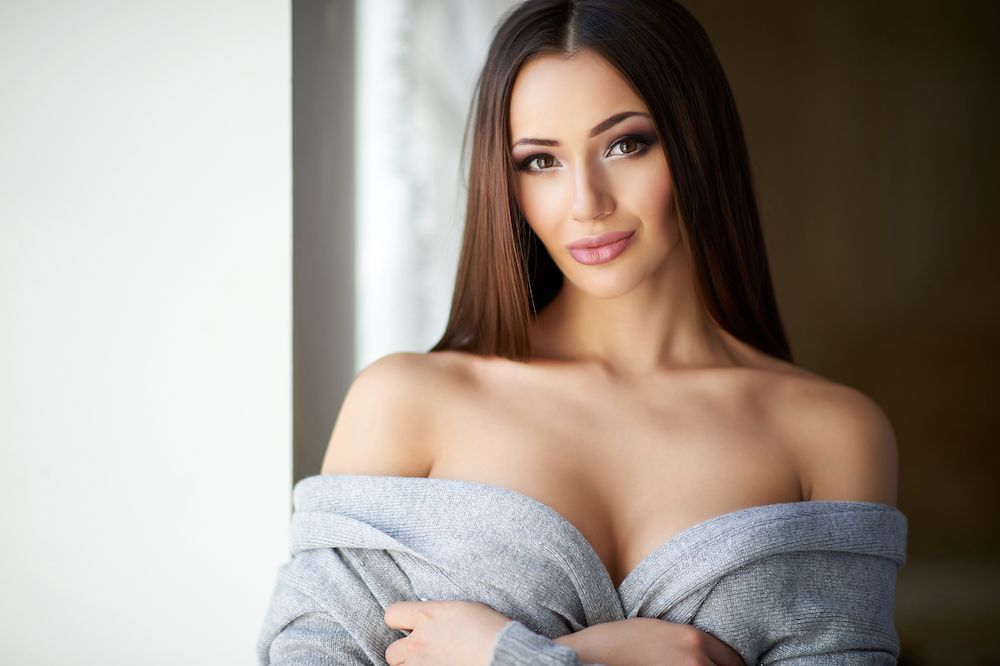 seductive brown-haired woman in grey off-the-shoulder sweater