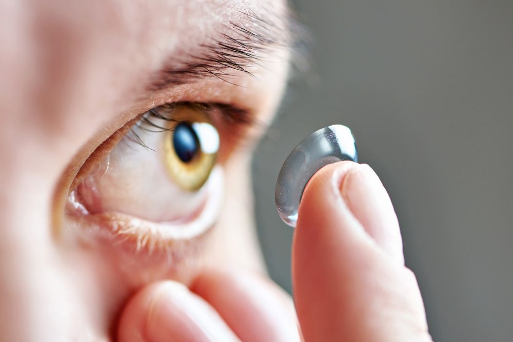 woman putting in contact lenses for astigmatism
