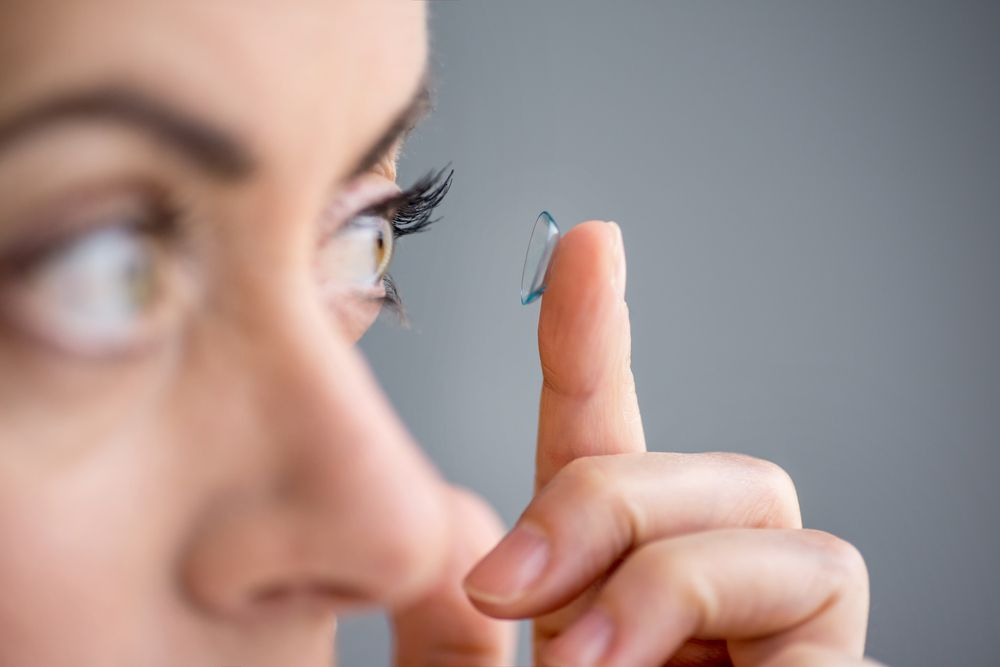 Girl put contact lenses on her eyes