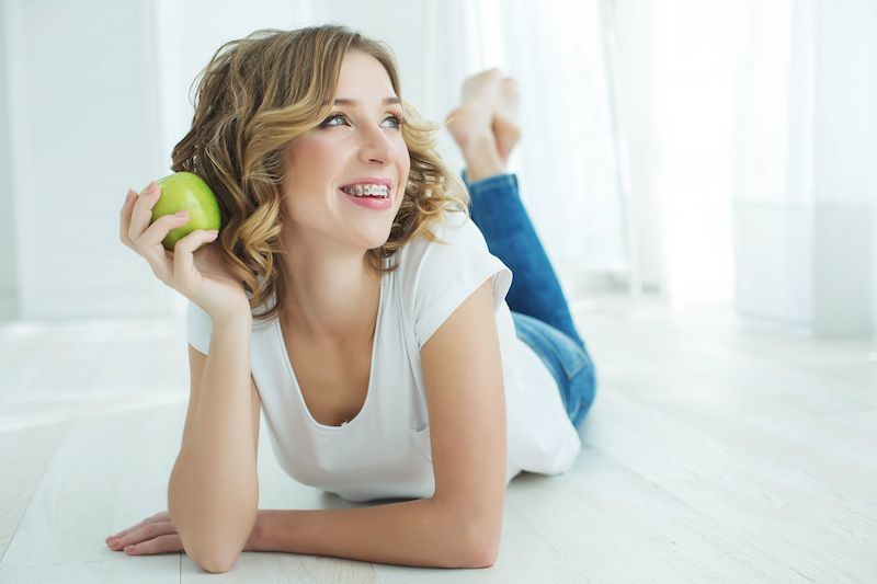 woman with braces eating an apple