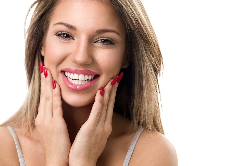 beautiful woman smiling and touching her face