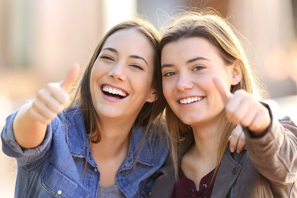 two funny friends with thumbs up