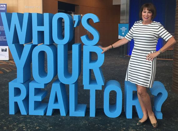 Gerri-Lynn Fives Standing Next to Who's Your Realtor Sign