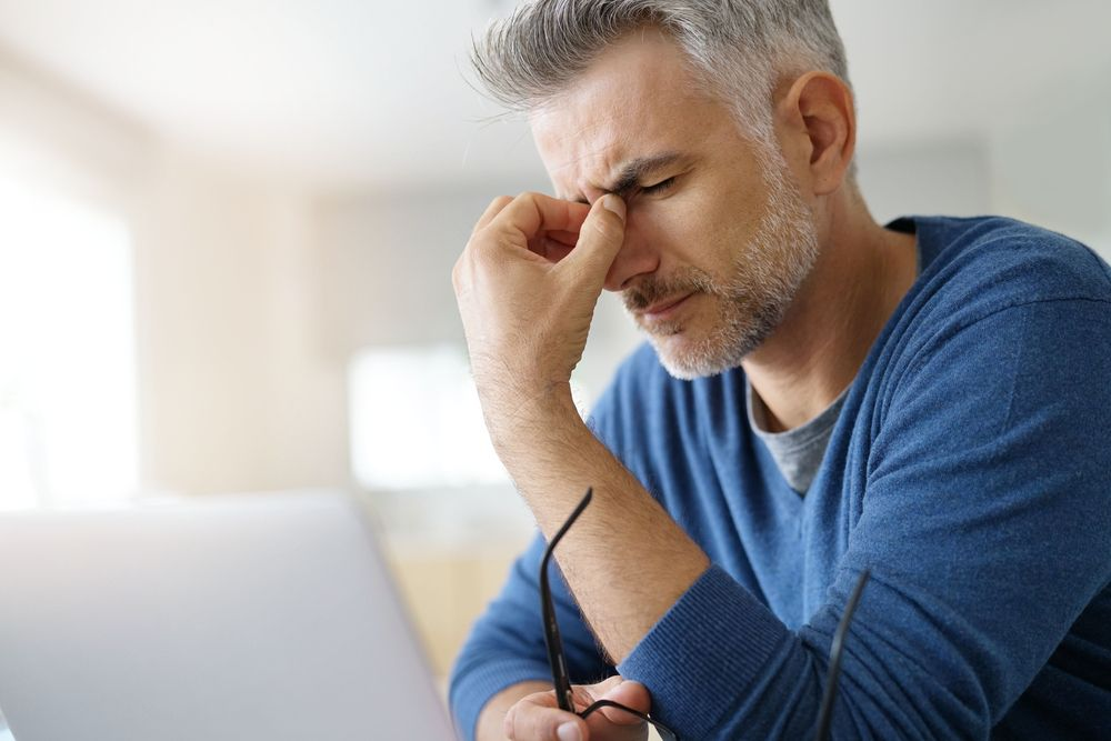 Man at home having a headache in front of laptop