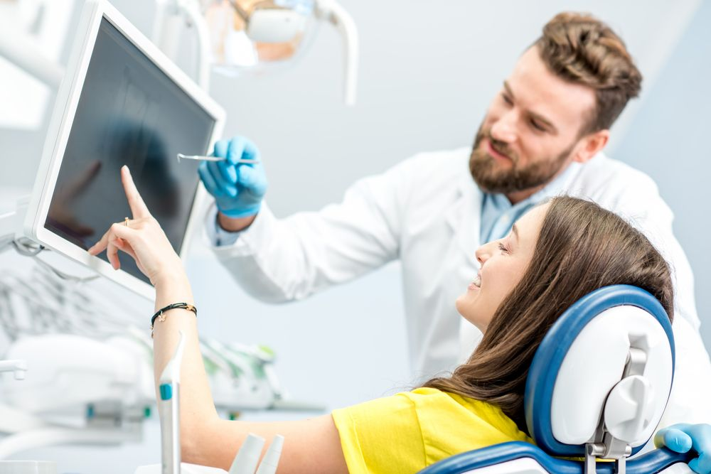 dentist showing results to patient​​​​​​​
