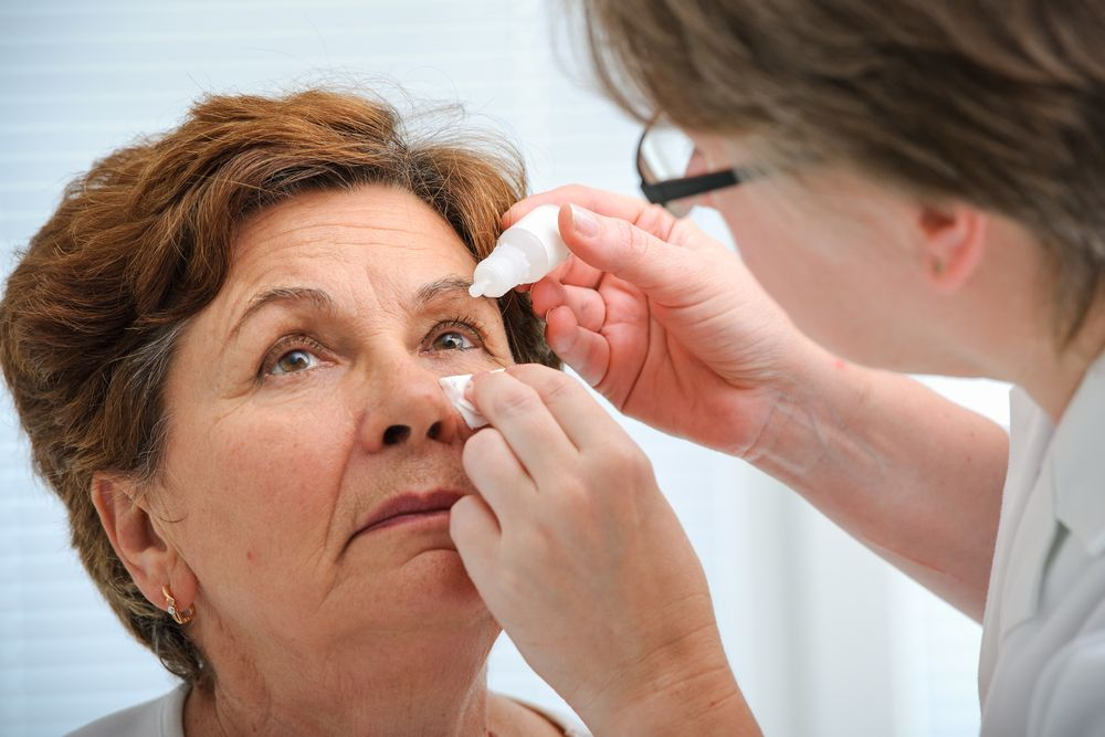 Doctor gives eye drop to patient