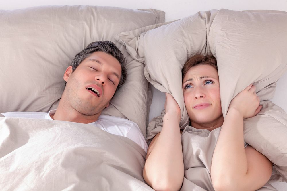 woman covers her ears with pillow because of snoring man
