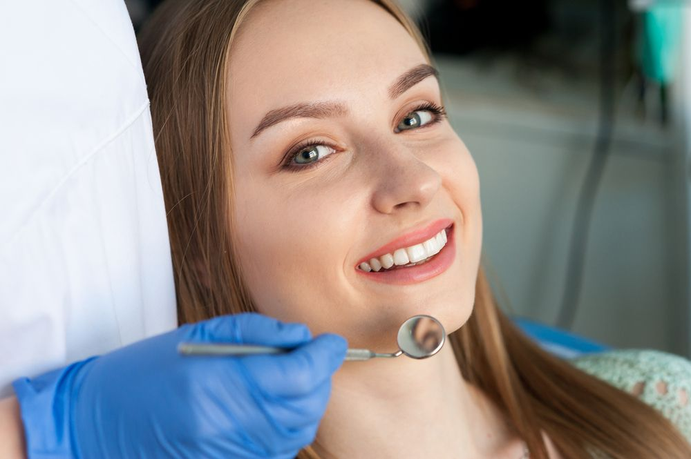 Beautiful smiling woman with dentist​​​​​​​