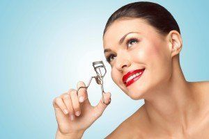 Beautiful woman with eyelash curler