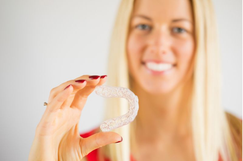Blonde Lady Holding Invisalign​​​​​​​