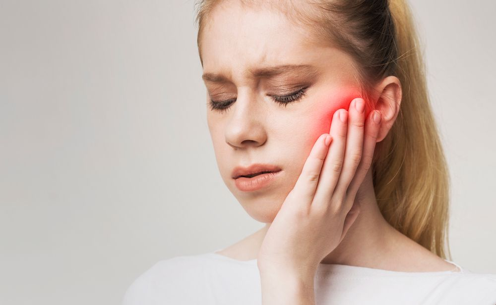 young blonde woman in mouth pain