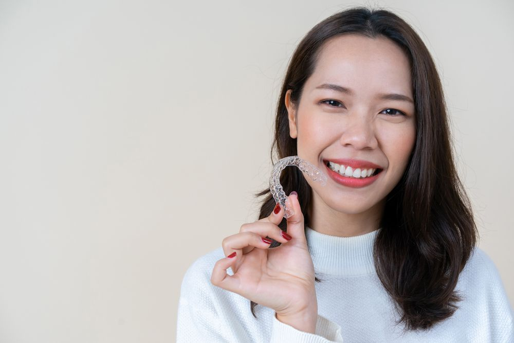 woman holding a mouthguard and smiling
