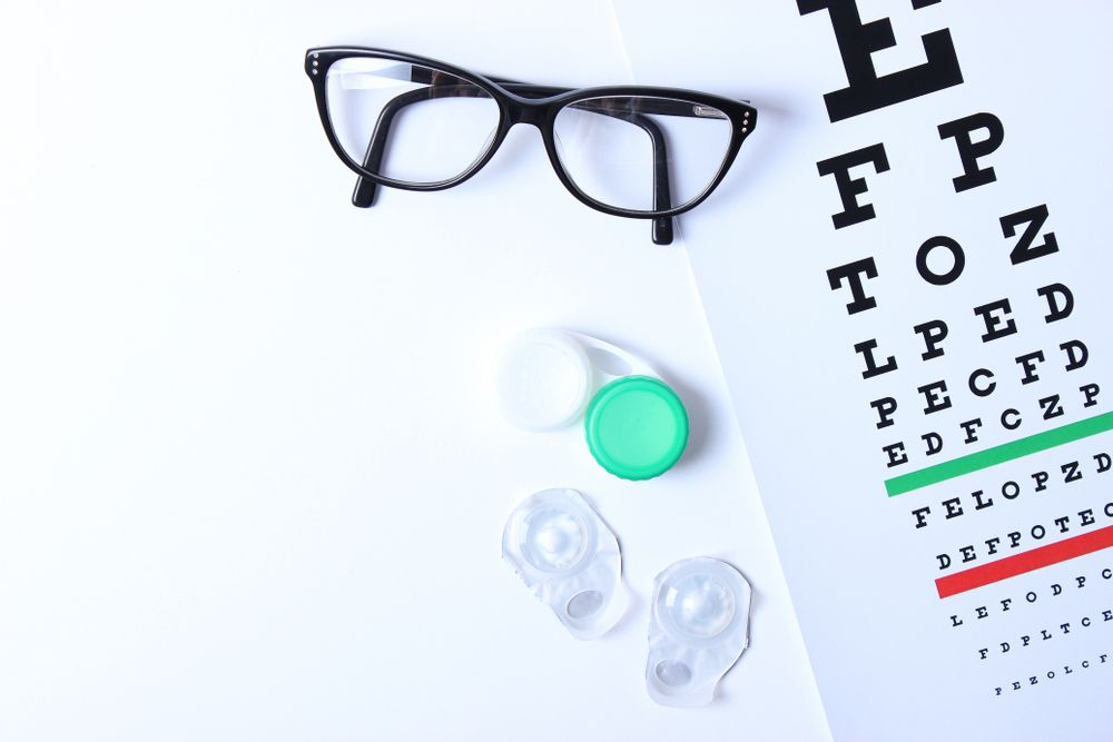 glasses and lenses for vision correction and a table for checking vision on a light background.