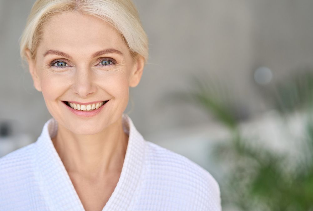 Older woman in white clothing smiling