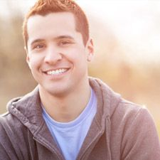 Young man smiles brightly into the camera