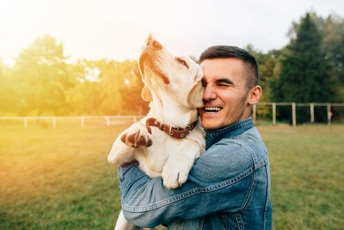 dog hugged by a man
