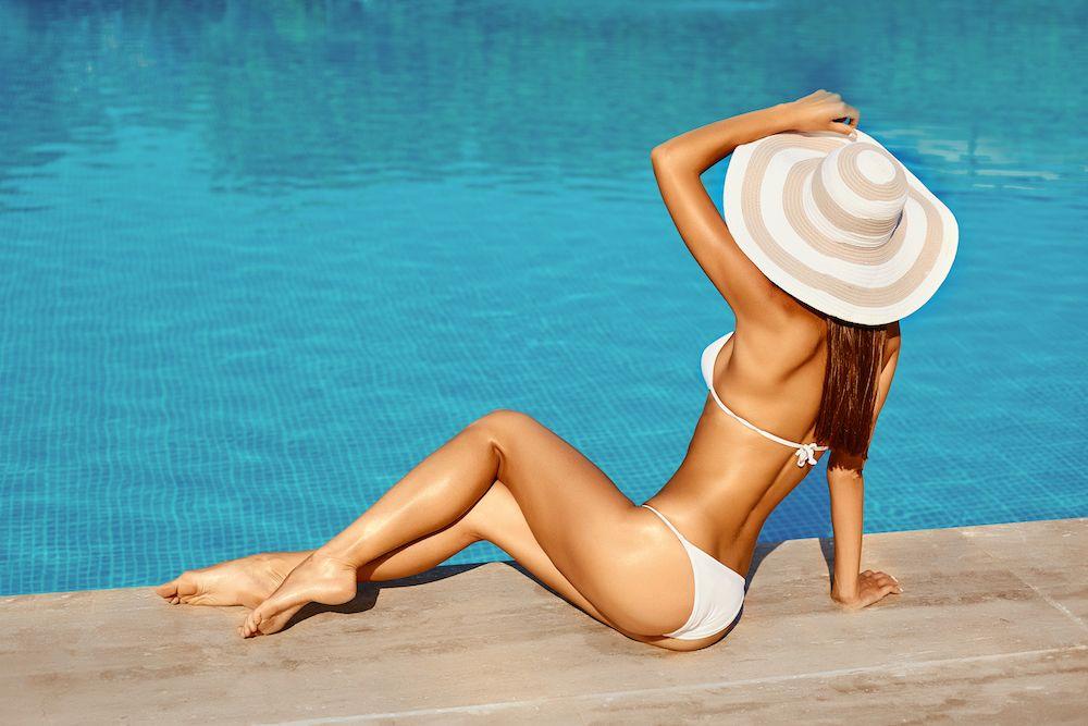 woman in a white bikini and oversized striped hat