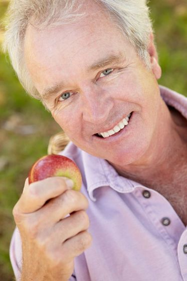 man smiling while holding an apple